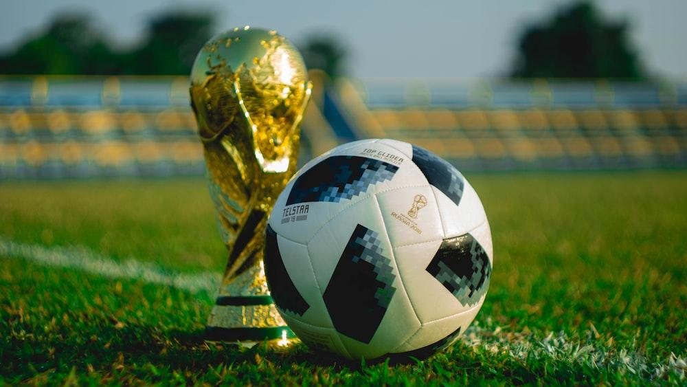 soccer ball beside trophy on soccer field
