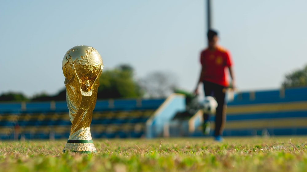 selective focus photography of gold-colored trophy on grass field during daytime