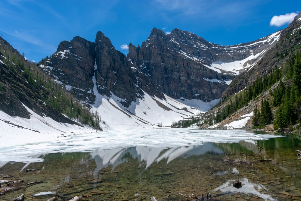 lake surrounded with mountain covered with snoe
