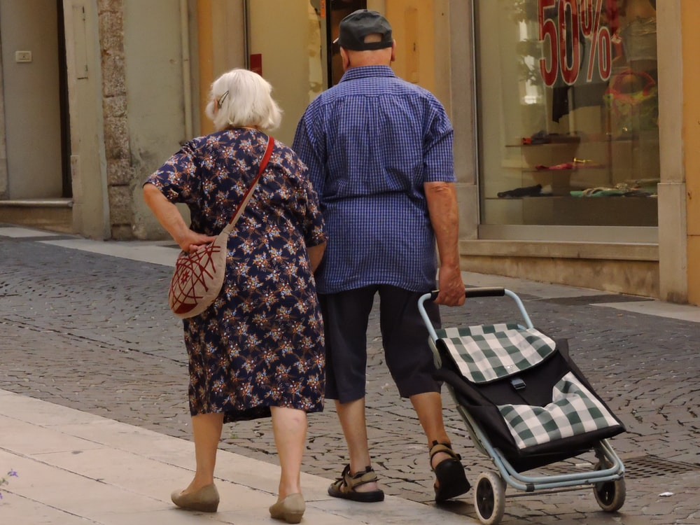 man and woman walking on street with stroller