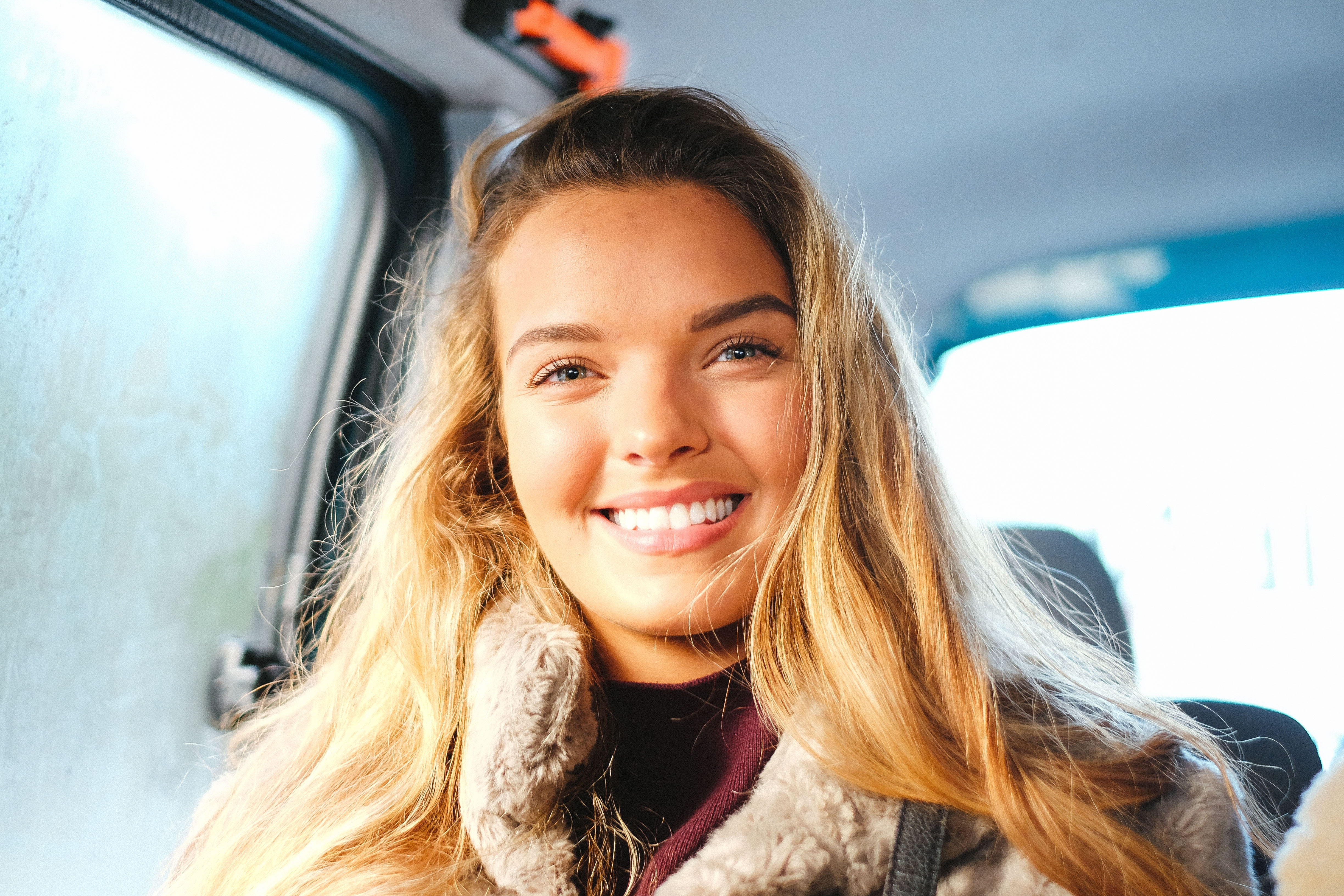 smiling woman sitting in vehicle