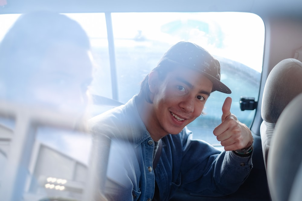 smiling man inside vehicle doing thumbs up during daytime