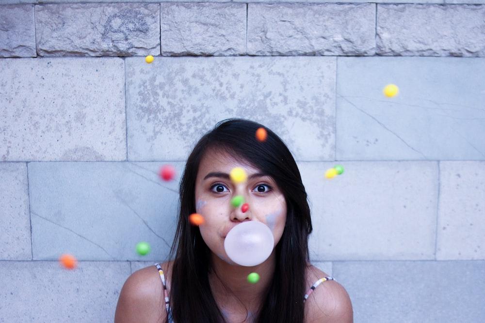 time lapse photo of woman making gum bubble