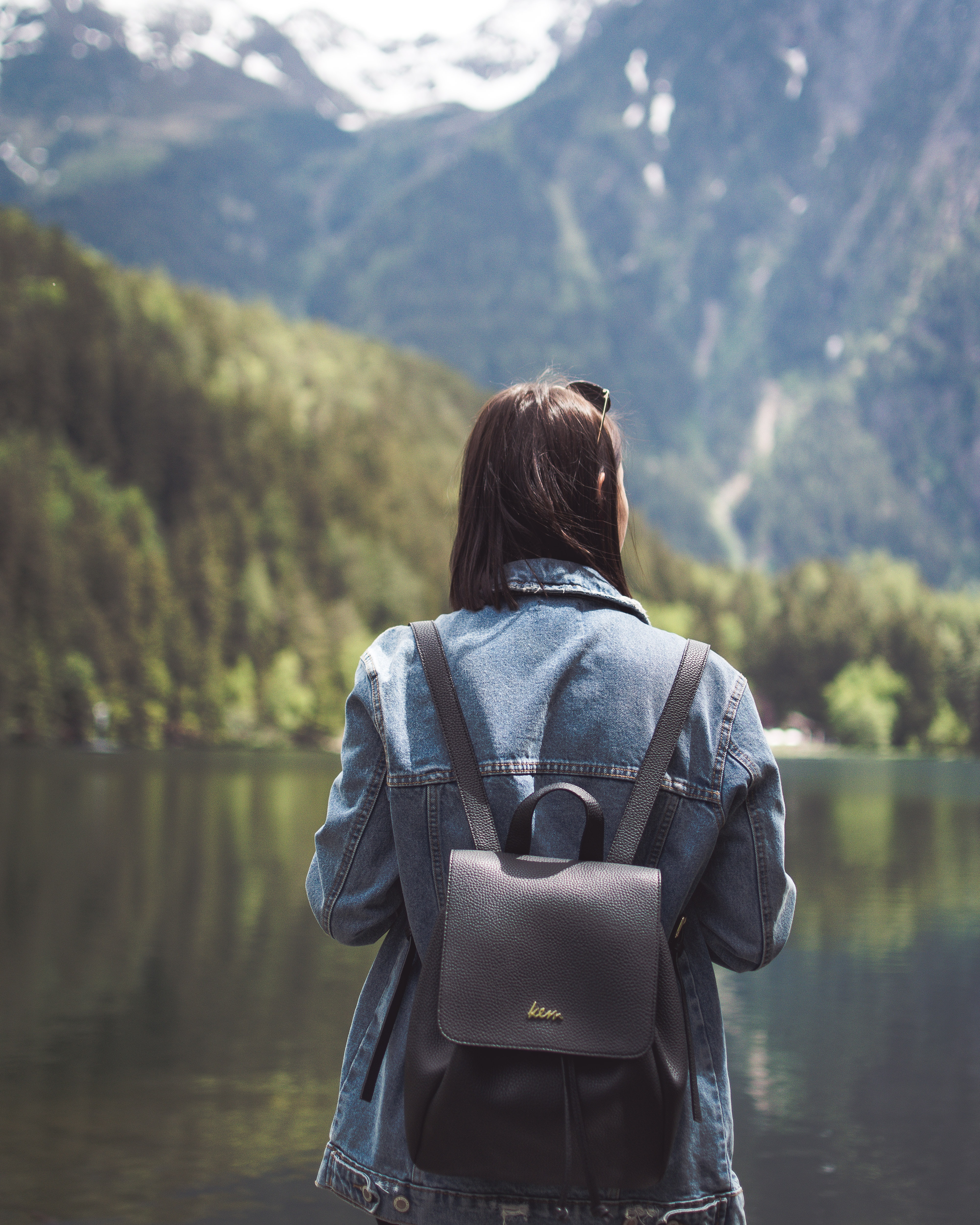 selective focus photography of woman wearing blue denim jacket and black bucket backpack near lagoon at daytime