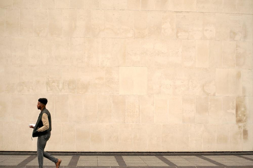 man walking on grey concrete pavement