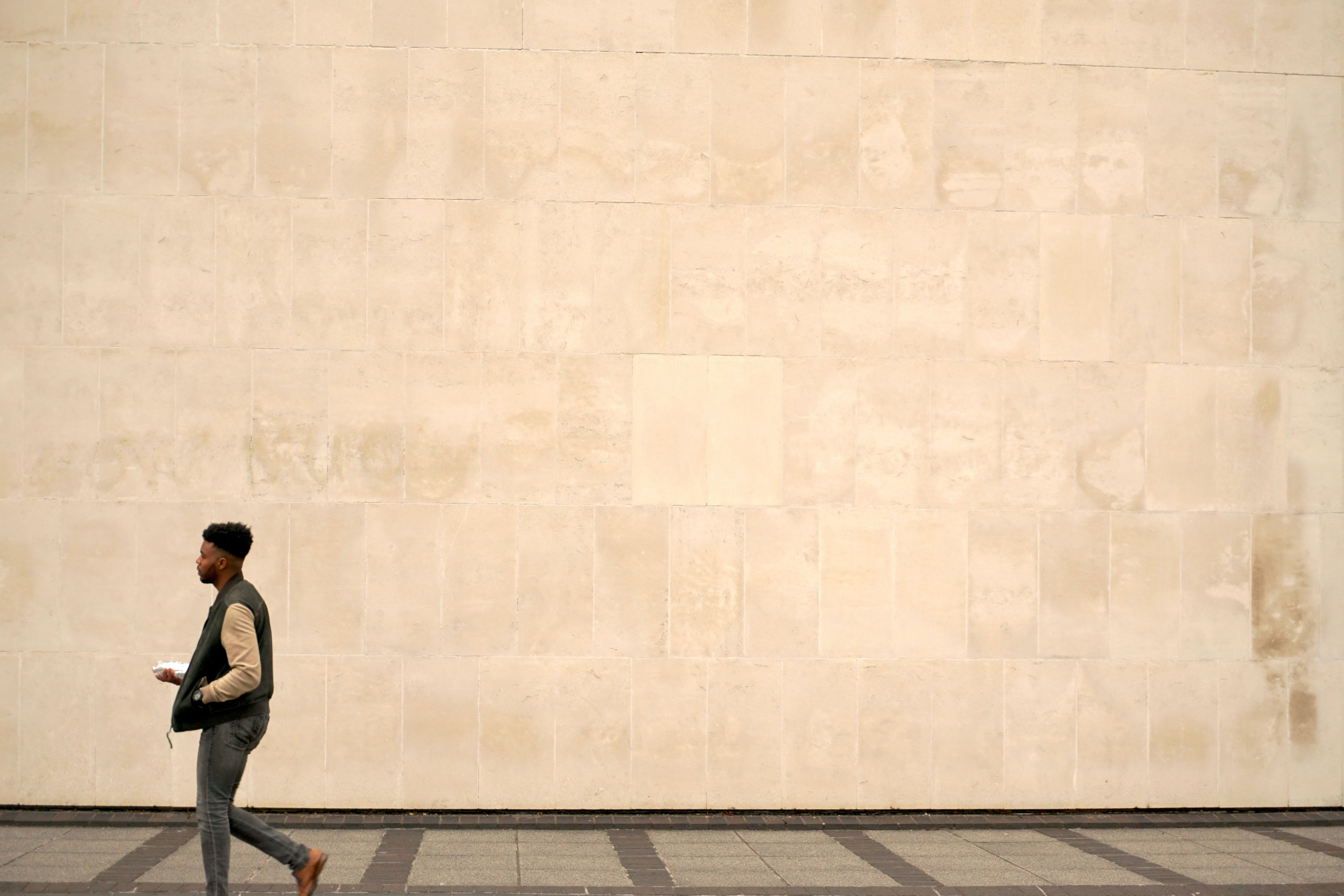 man walking on grey concrete pavement