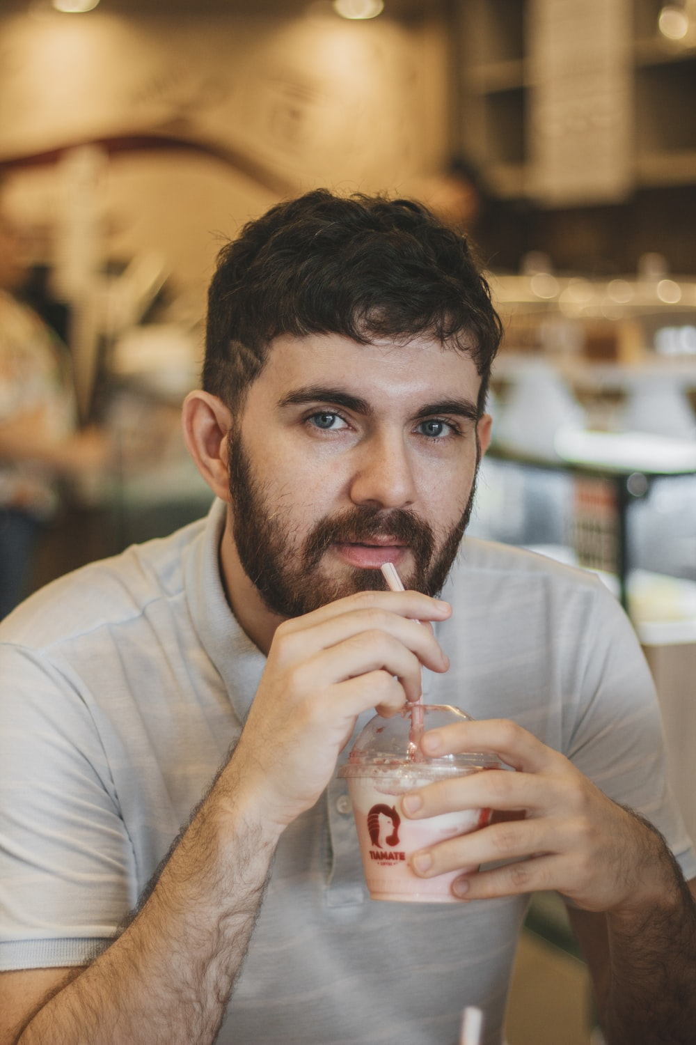 selective focus photography of man drinking smoothie