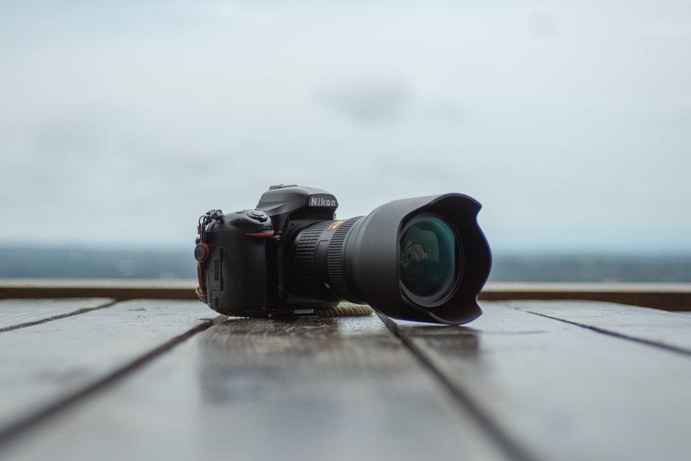 black Nikon DSLR camera on wooden plank floor shallow focus photography