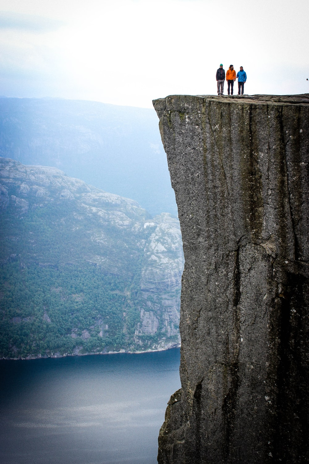 three people standing on cliff