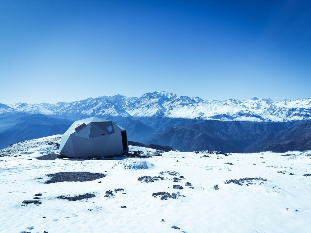 gray dome tent on snow surface overlooking snow capped mountain under blue sky at daytime