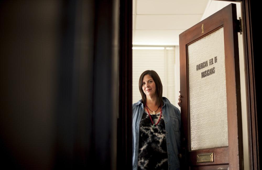 woman standing beside wooden door