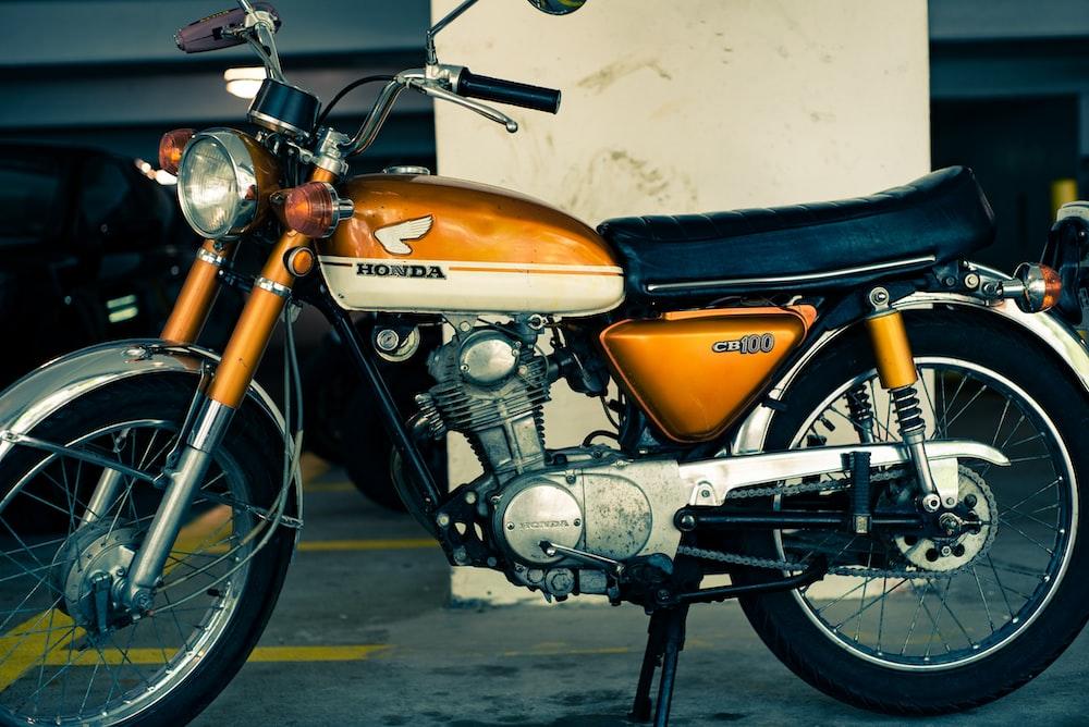 orange and black Honda standard motorcycle