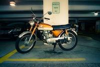 person taking photo of orange Honda standard motorcycle