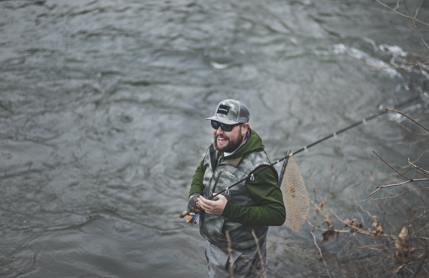 Man holding a fishing rod and net while standing at the river side