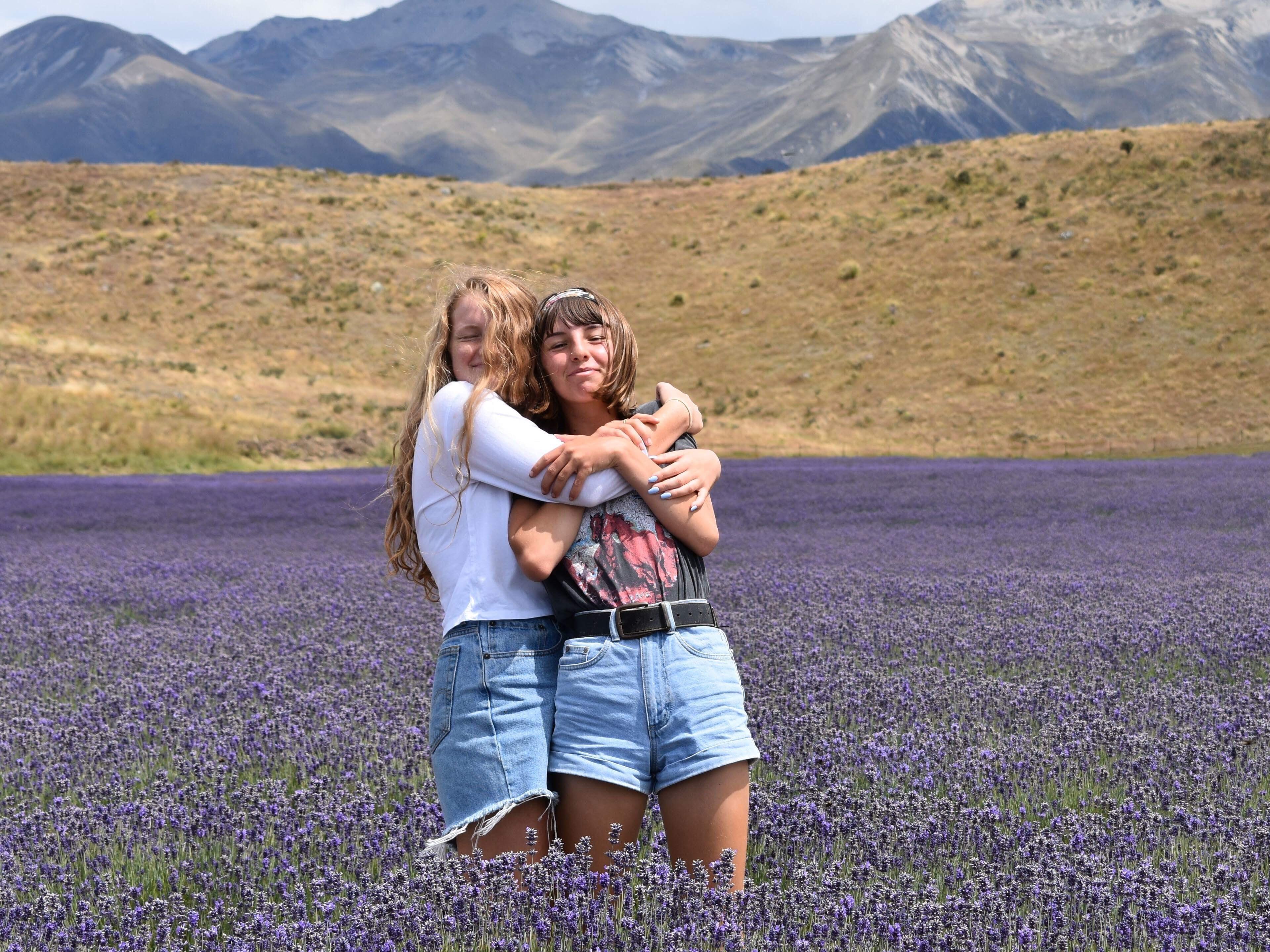 woman hugging another woman on purple flower field