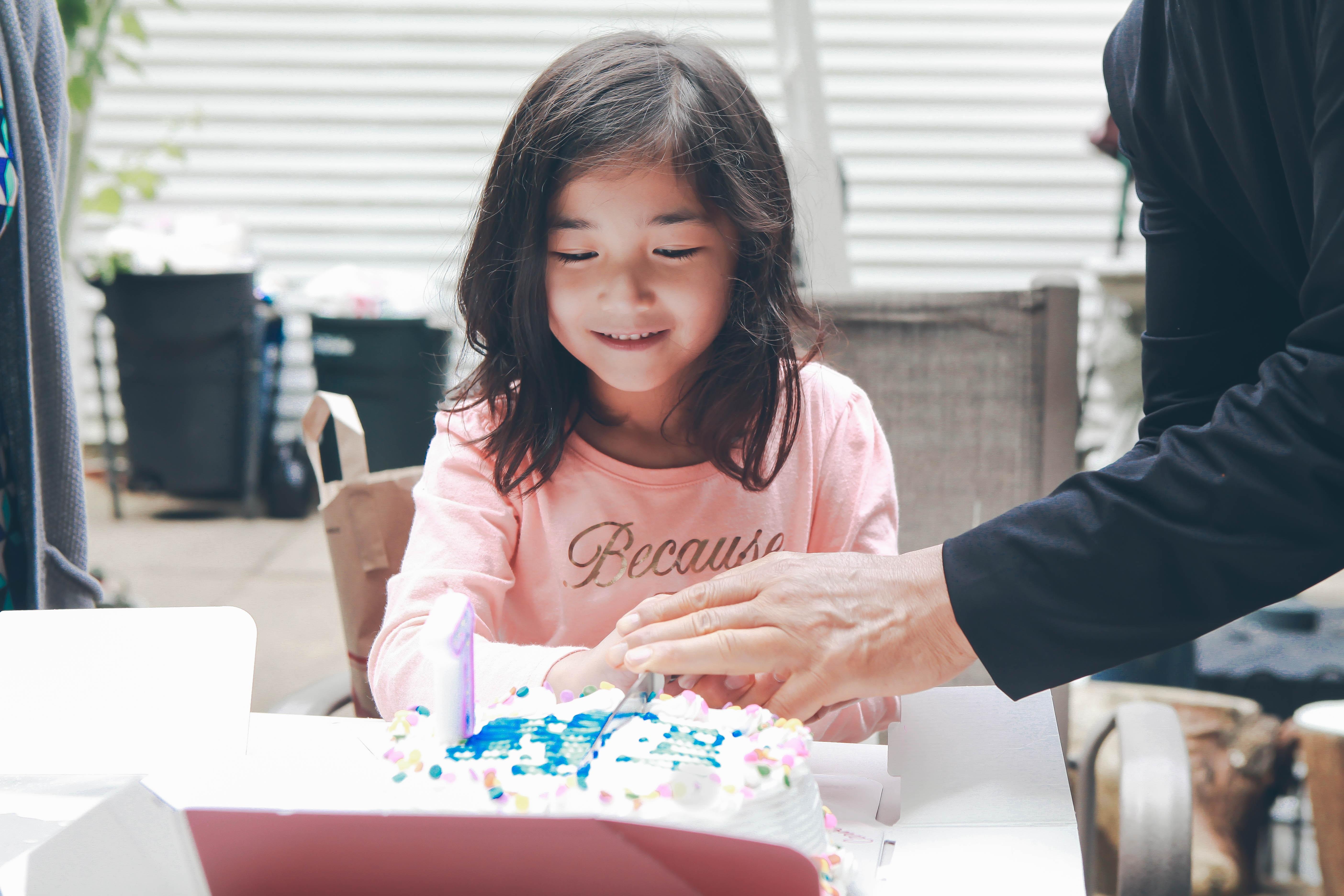 girl wearing pink crew-neck sweatshirt opening white-icing covered cake