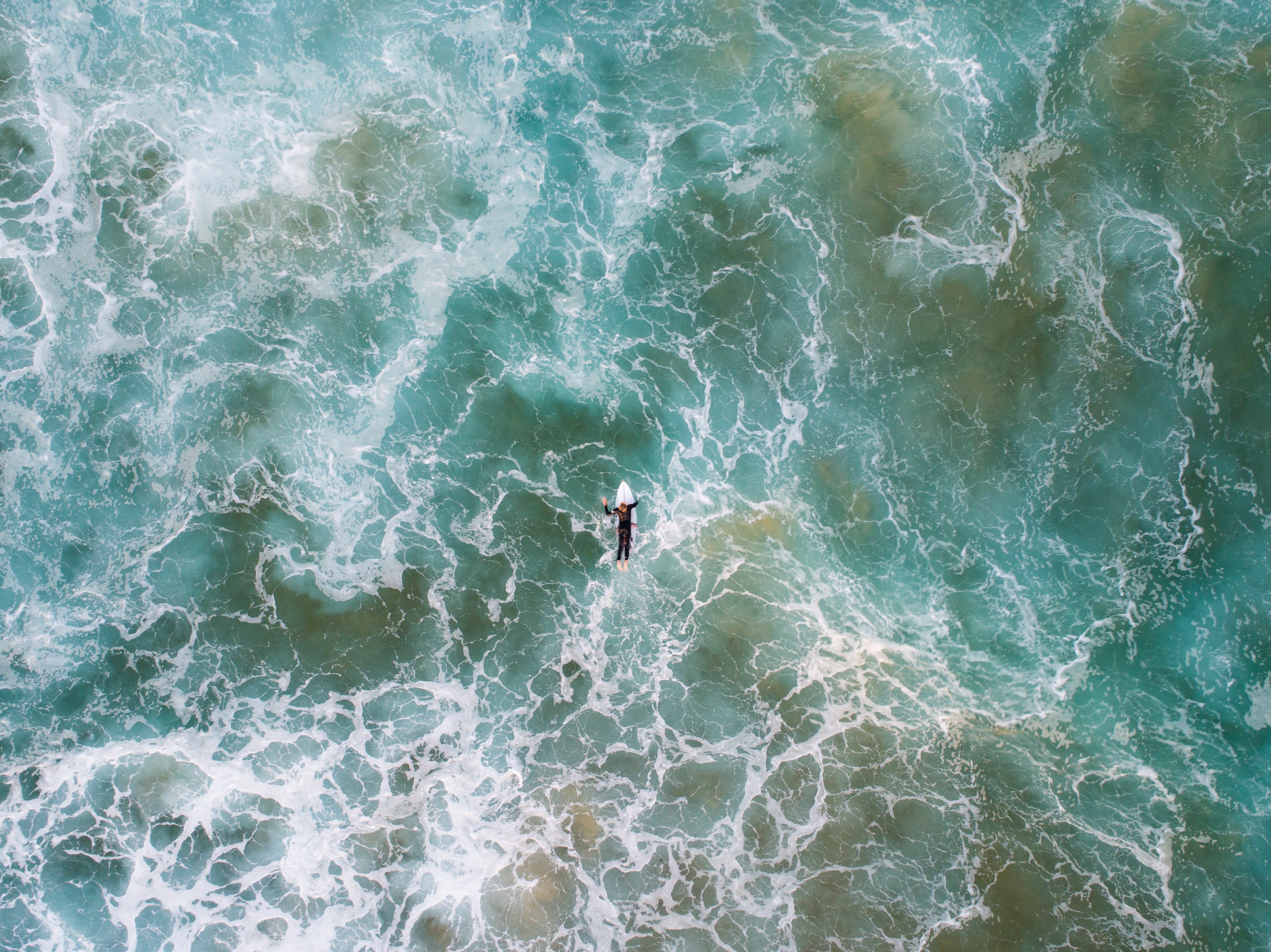 bird's-eye view photo of man surfing on body of water