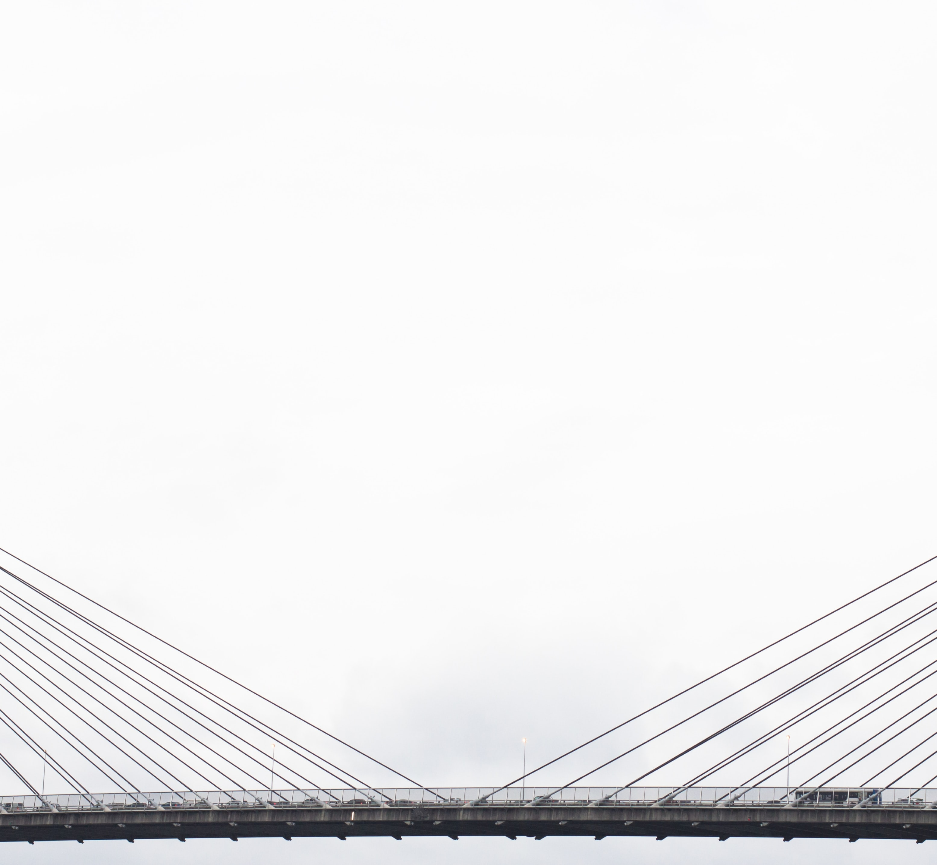 vehicles on grey suspension bridge under cloudy sky during daytime