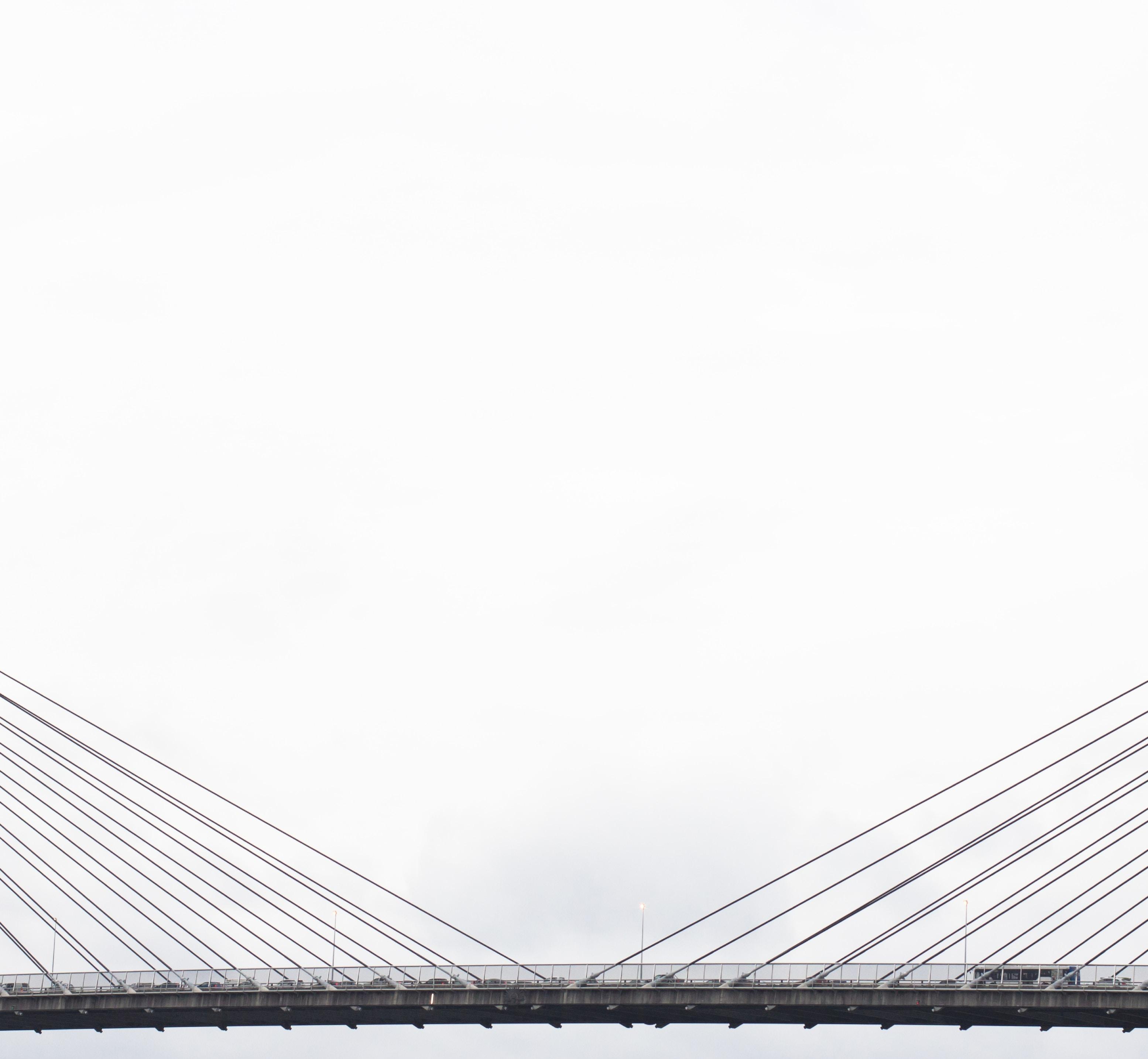 vehicles on grey suspension bridge under cloudy sky during daytime