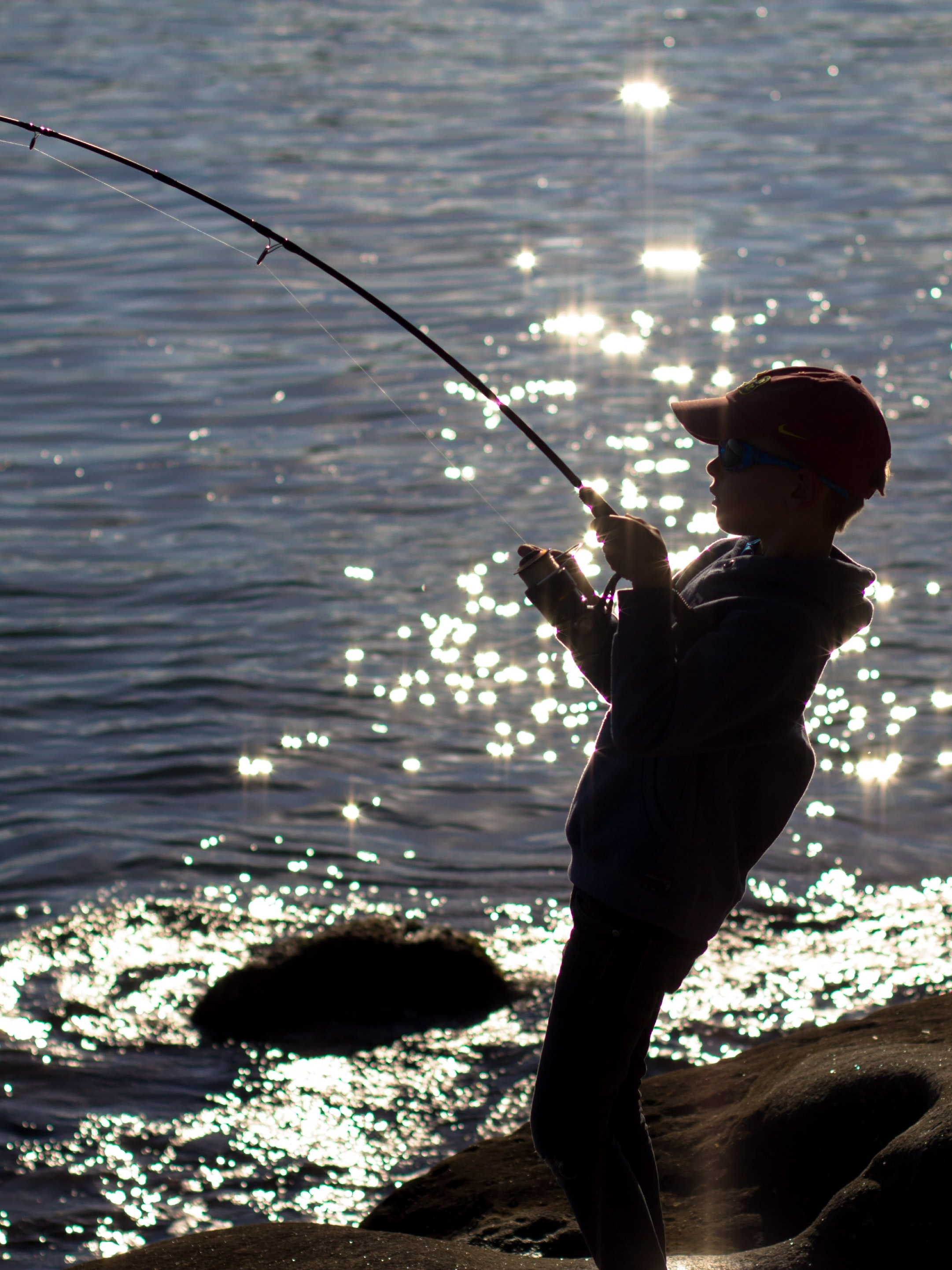 silhouette of boy fishing on shore