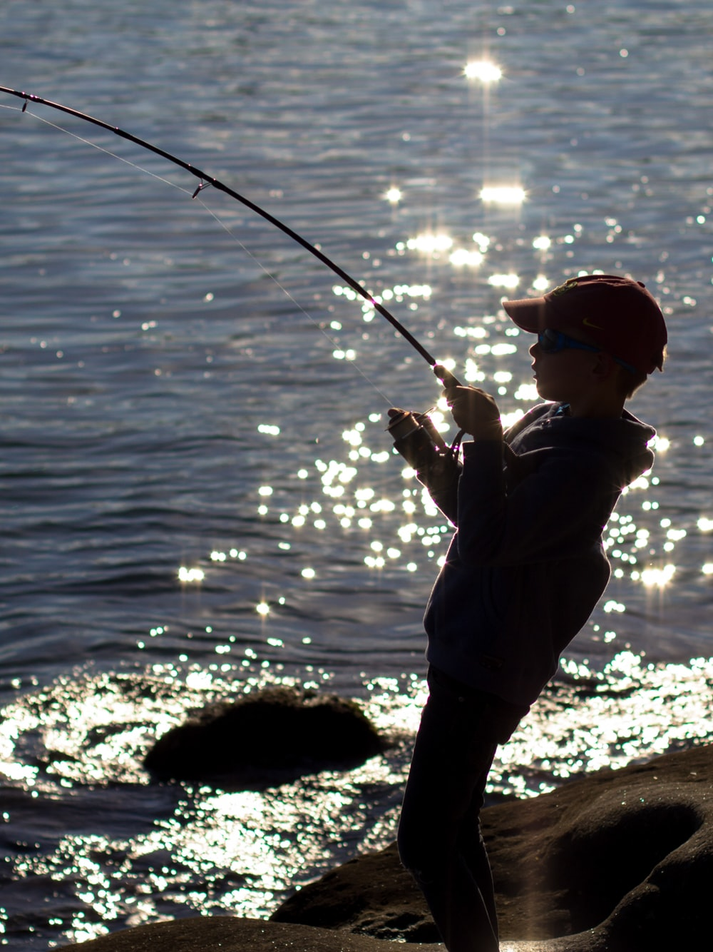 silhouette of boy fishing on shore