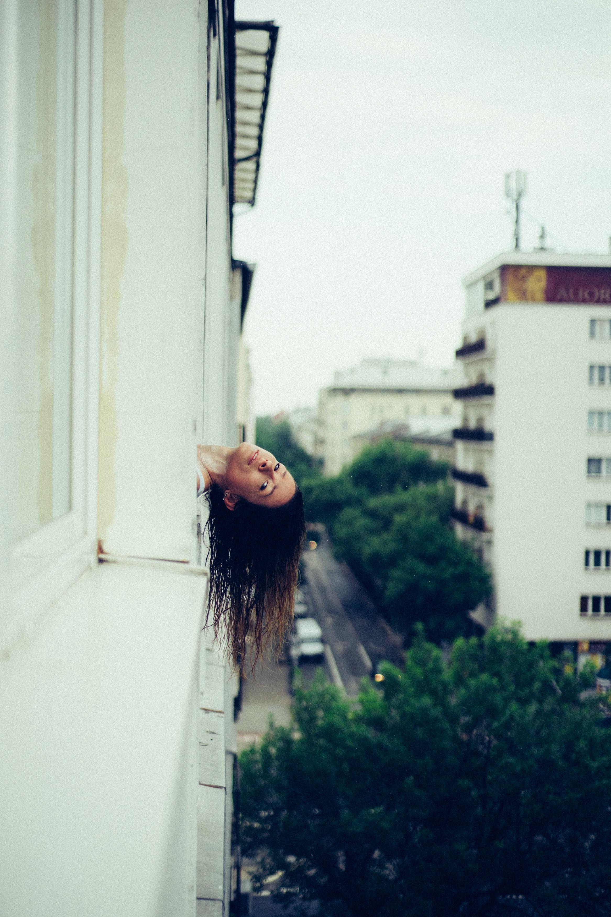 woman with hear head outside the window