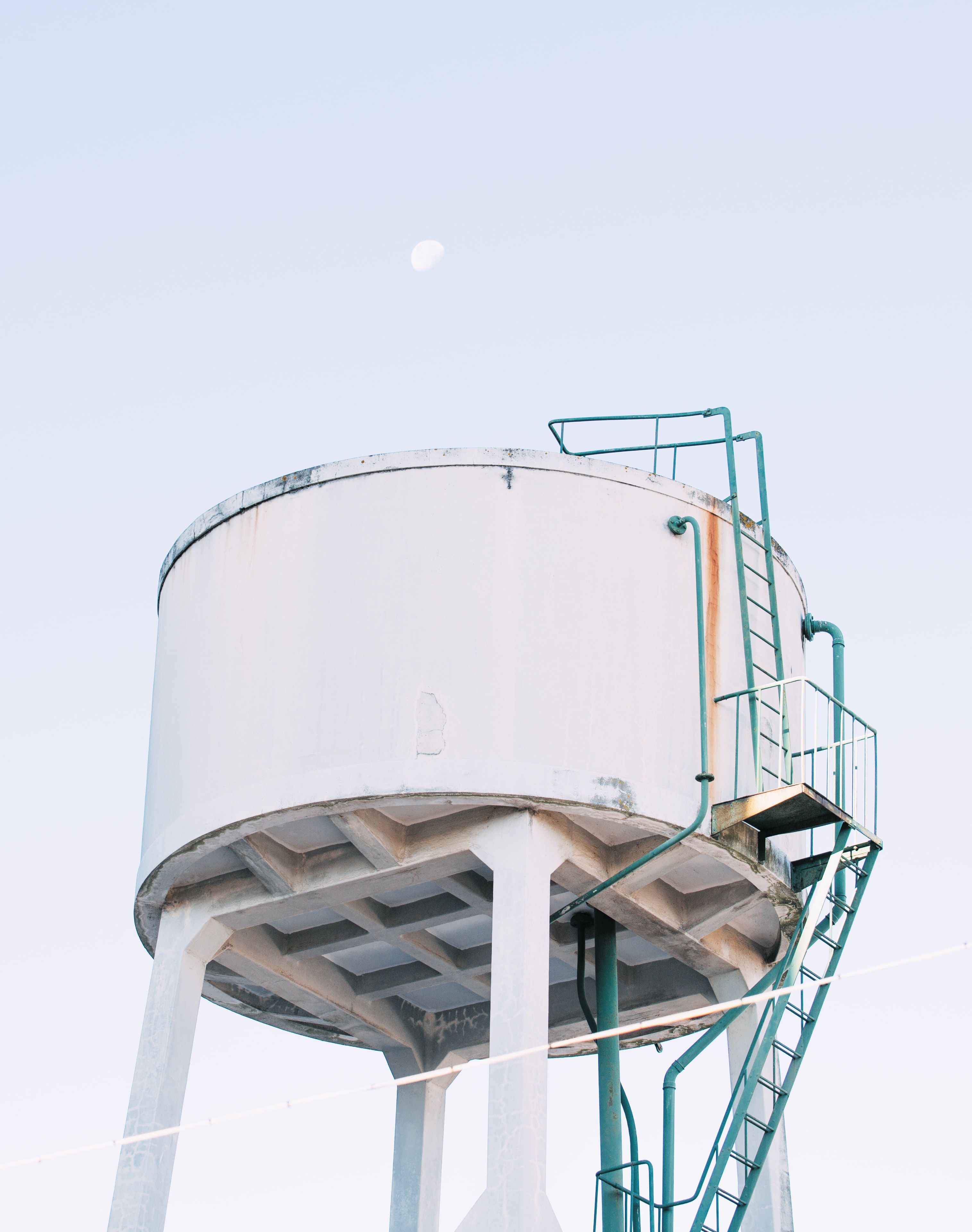 large round white concrete fluid tank with green metal ladder