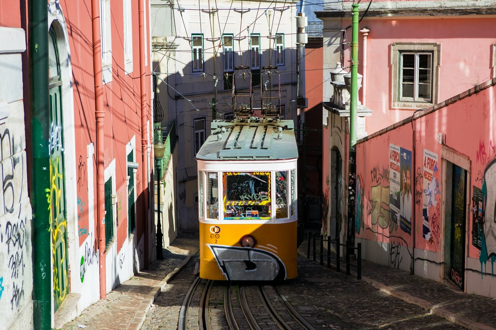 yellow and white tram between pink walls during daytime