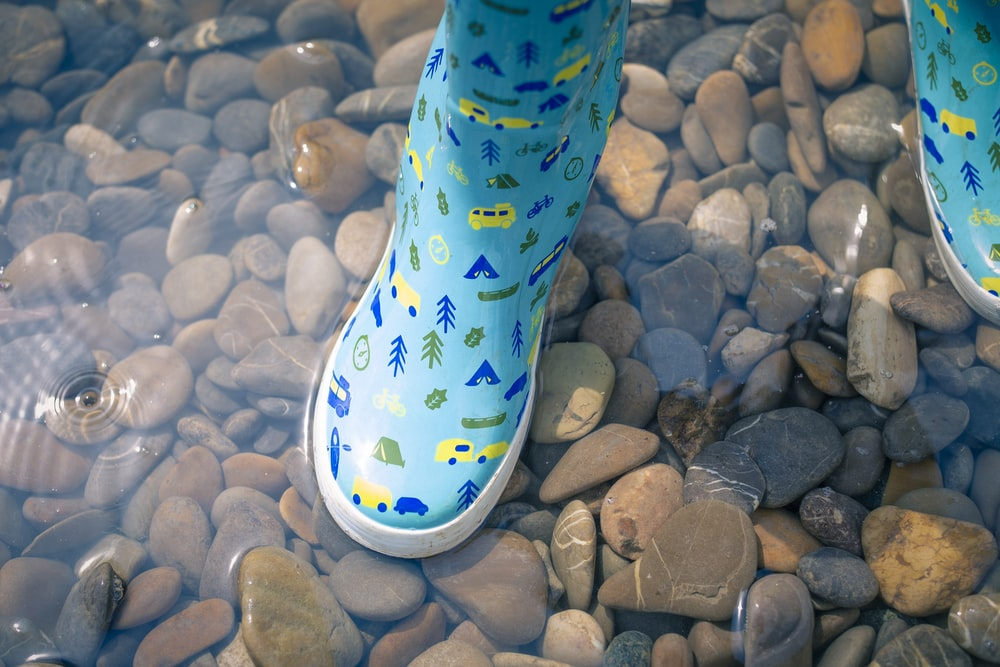 person wearing blue-green-and-yellow rain boots