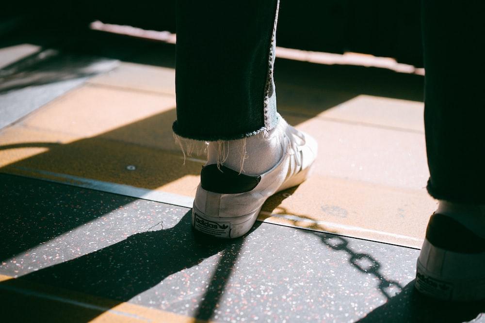 person wearing white low-top sneakers standing on brown wooden floor room