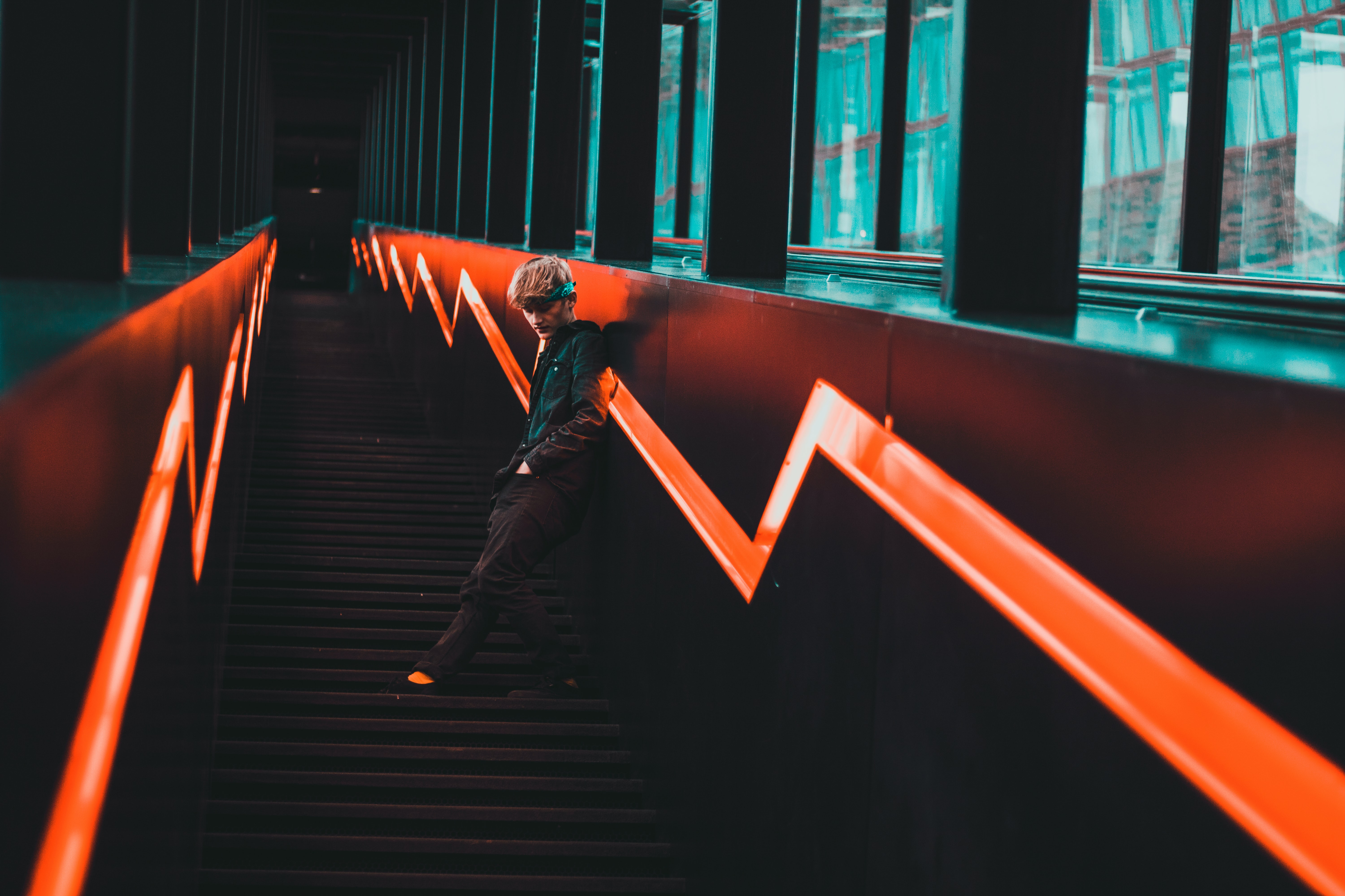 man leaning on stair railings during night time