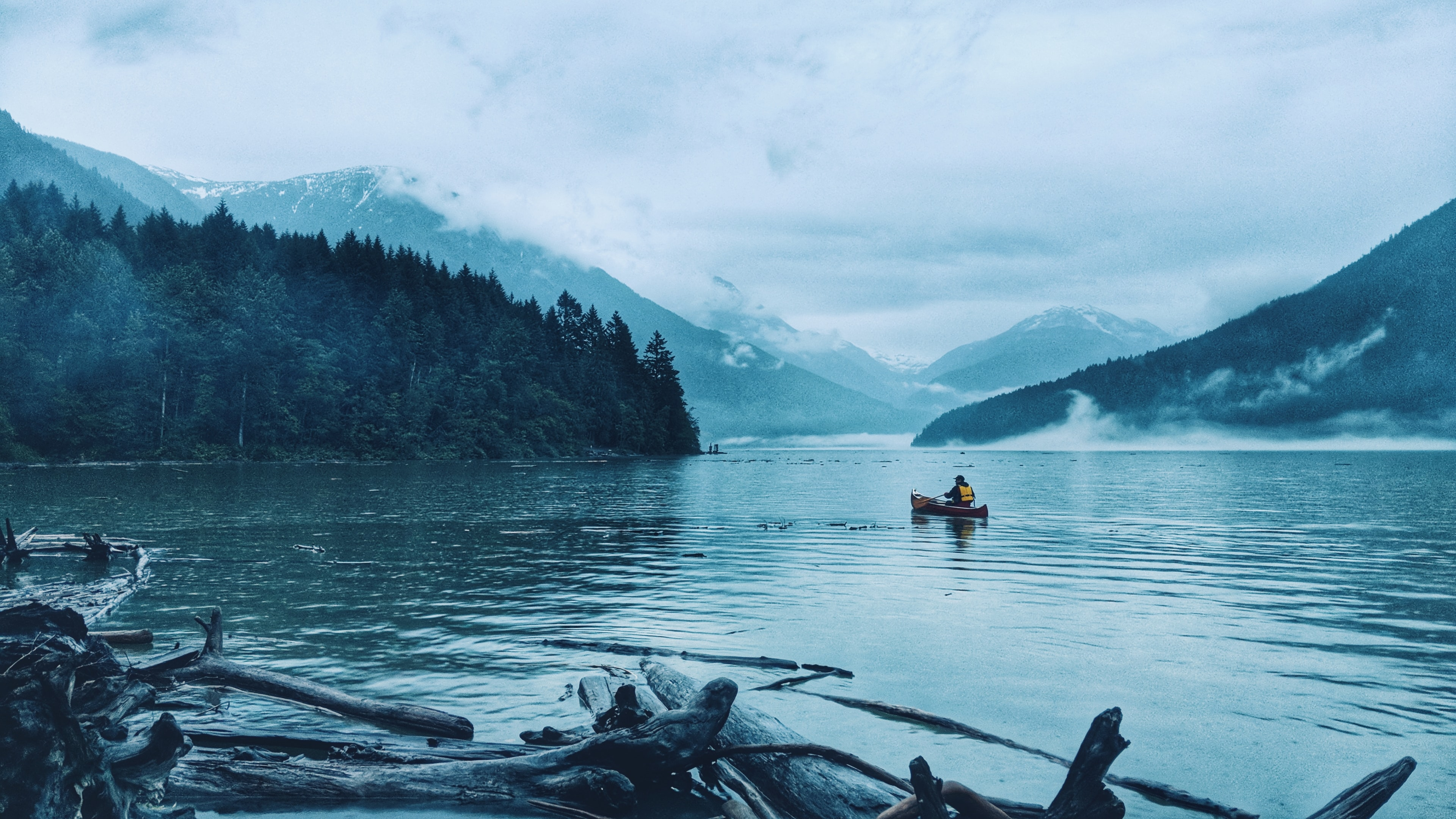 person riding canoe in the middle of lake