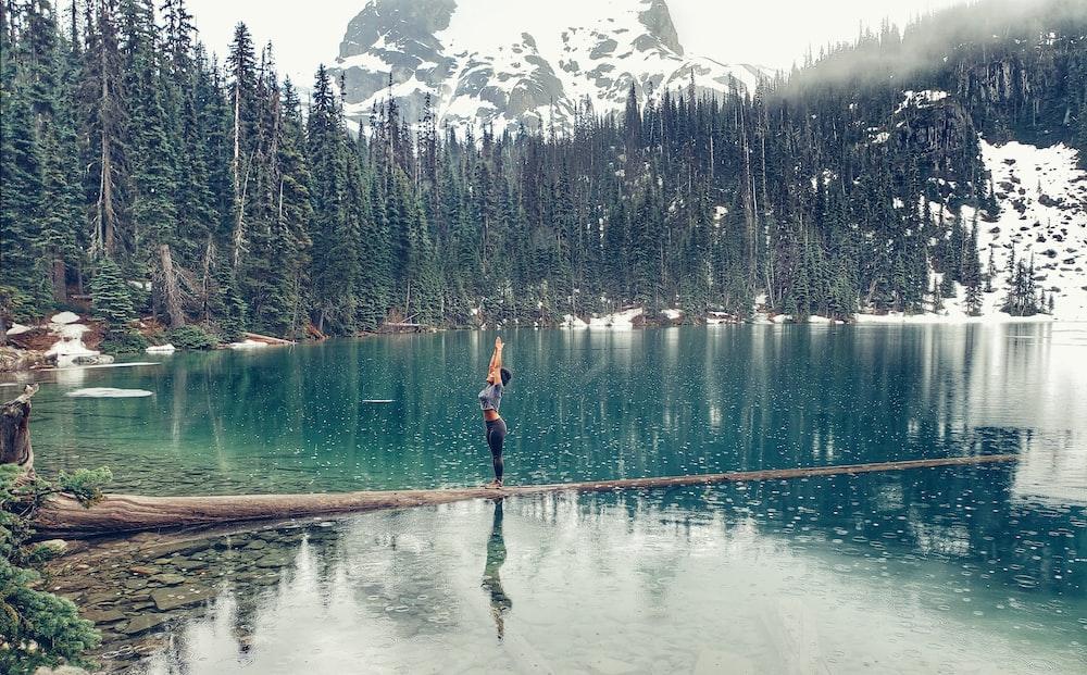 woman standing beside body of water