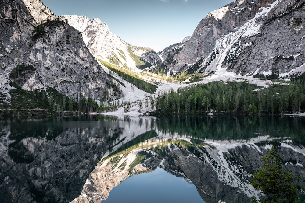 mountain reflected on body of water at daytime