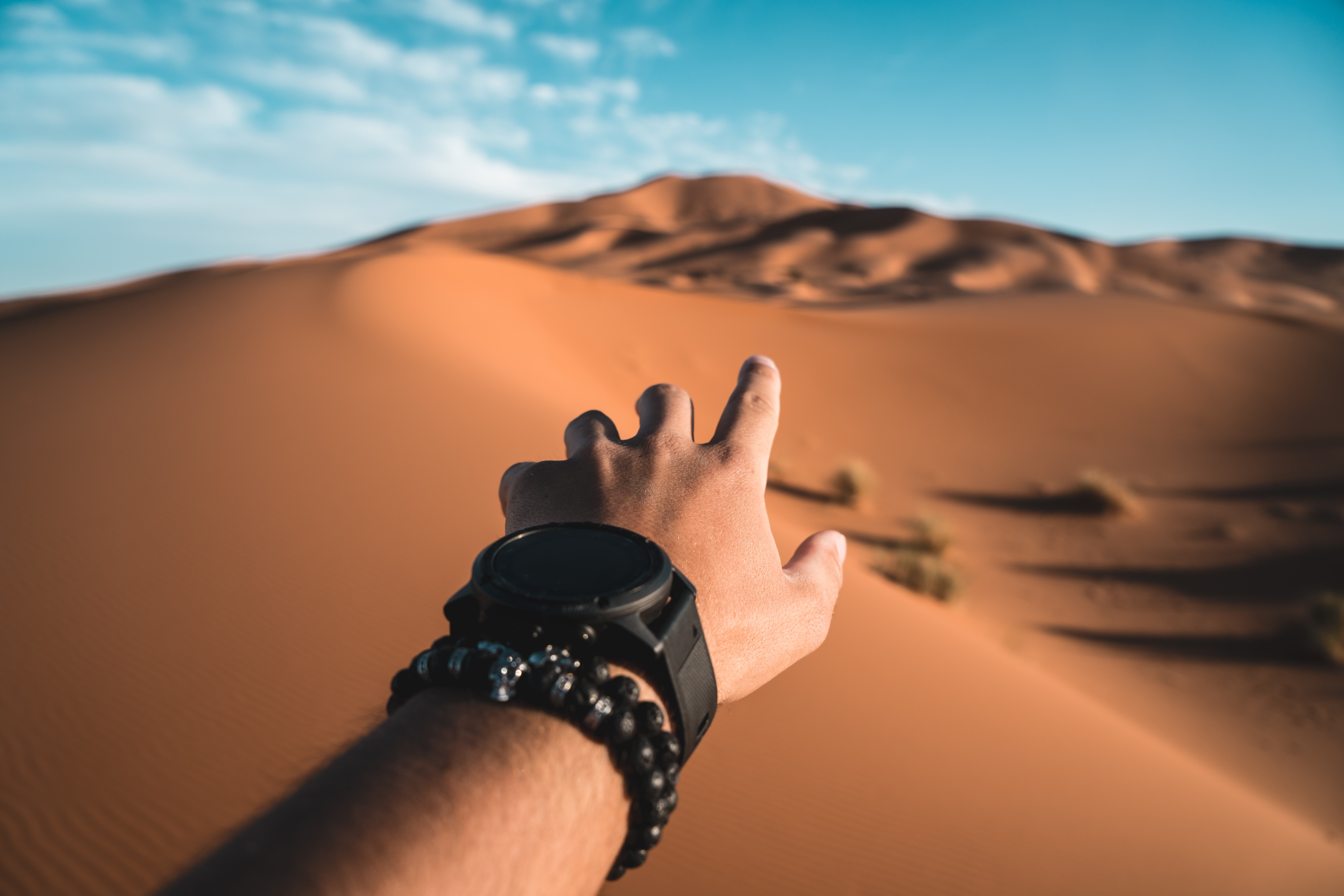 person pointing to dessert dune during daytime
