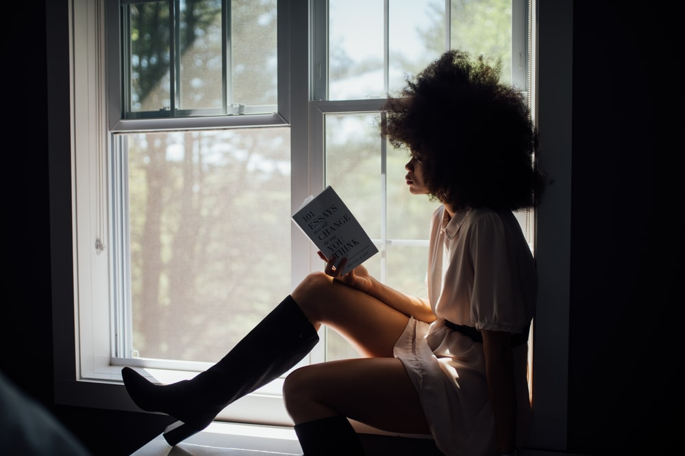 woman in white top holding book
