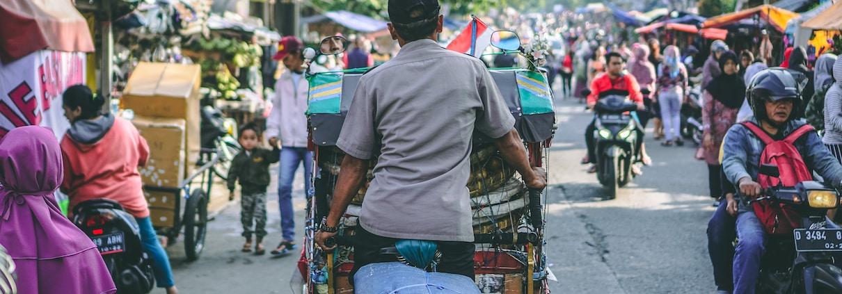 selective photography of man pedaling wagon