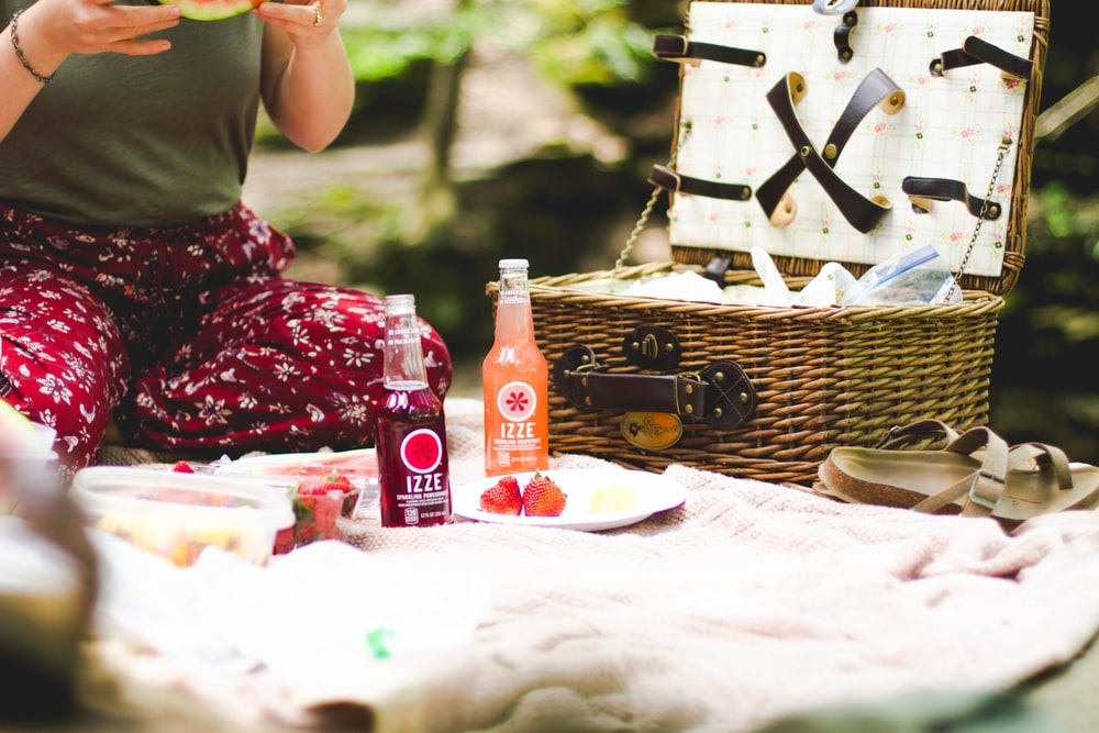 picnic basket beside two Ezze bottles on blanket