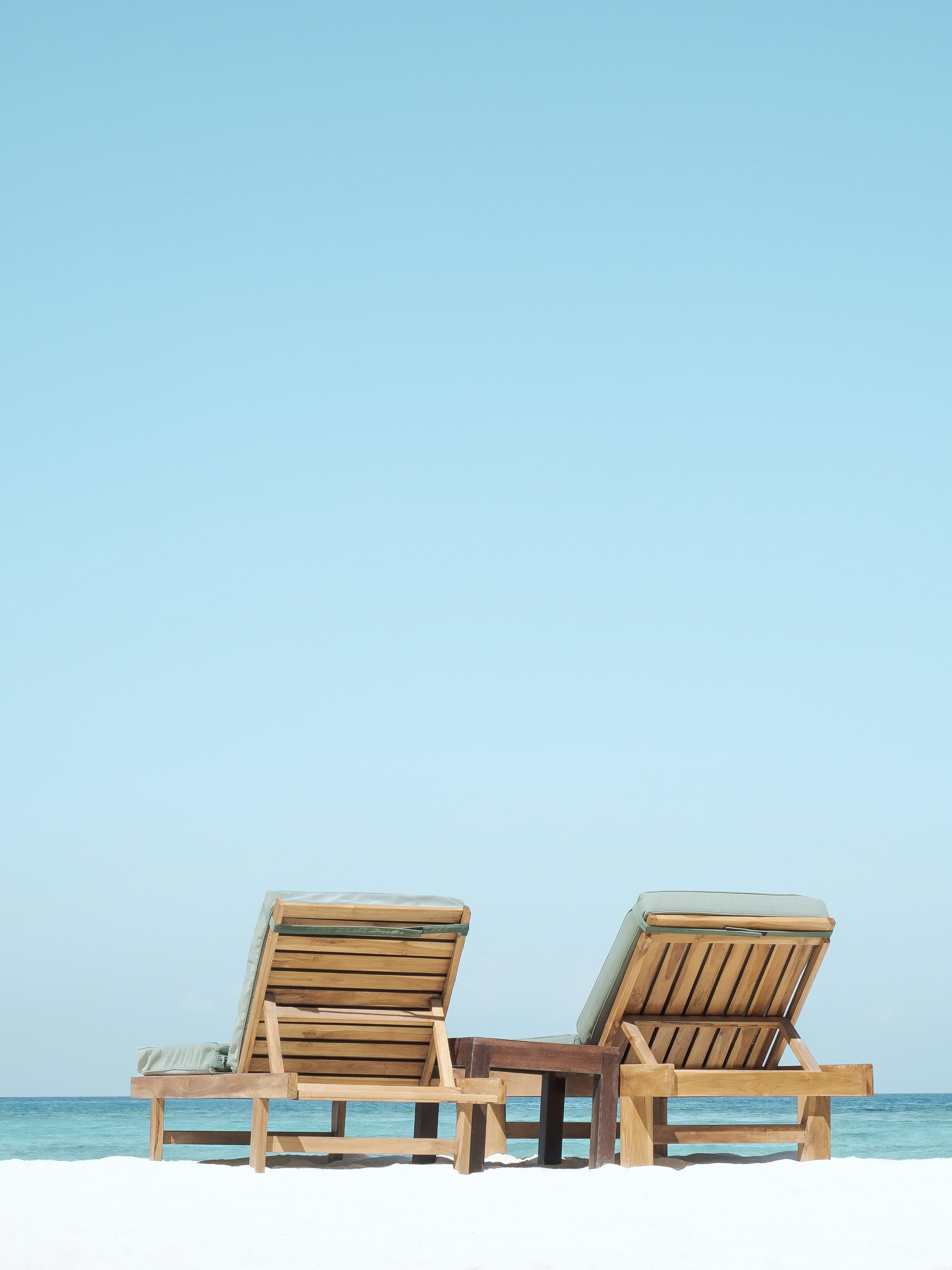 two brown wooden outdoor chaise loungers on beach