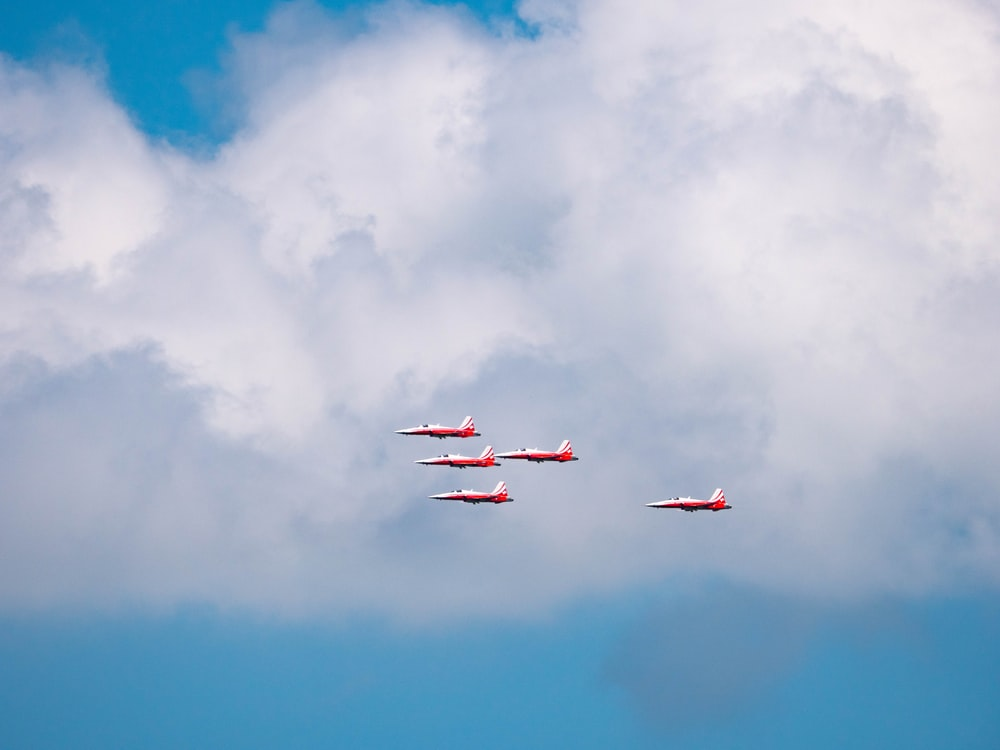 five red-and-white planes in flight