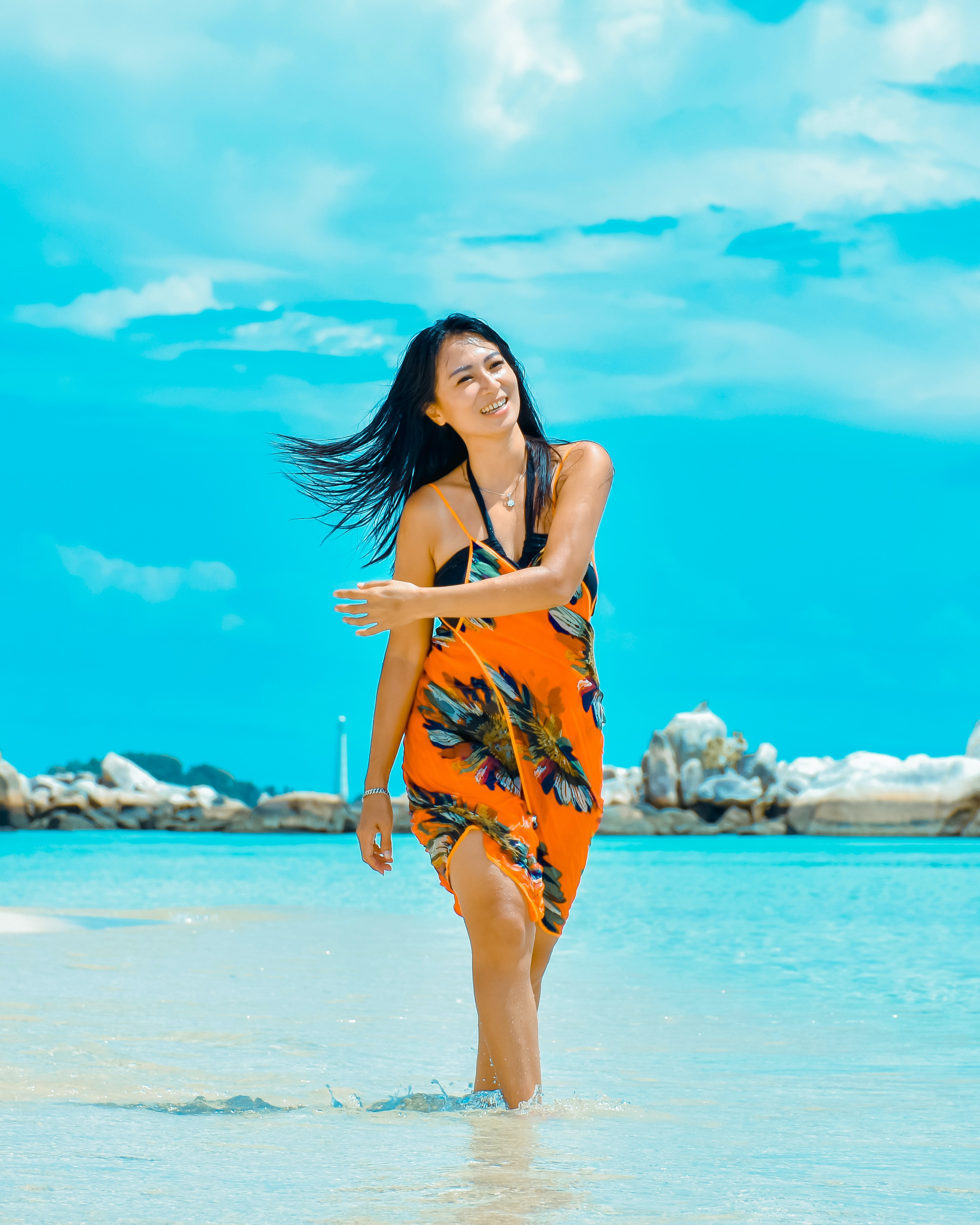 woman standing in seashore under white and blue sky during daytime