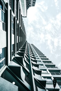 low angle photography of grey concrete building under white clouds at daytime