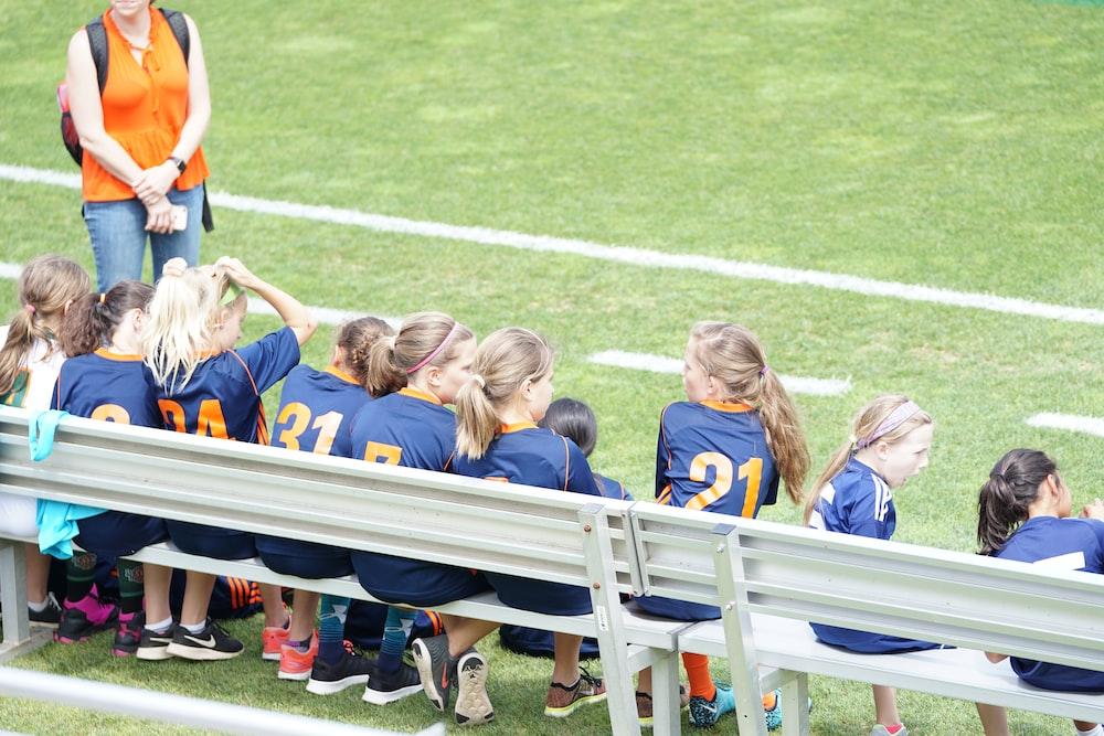 all girl football team sitting on white bench beside green field