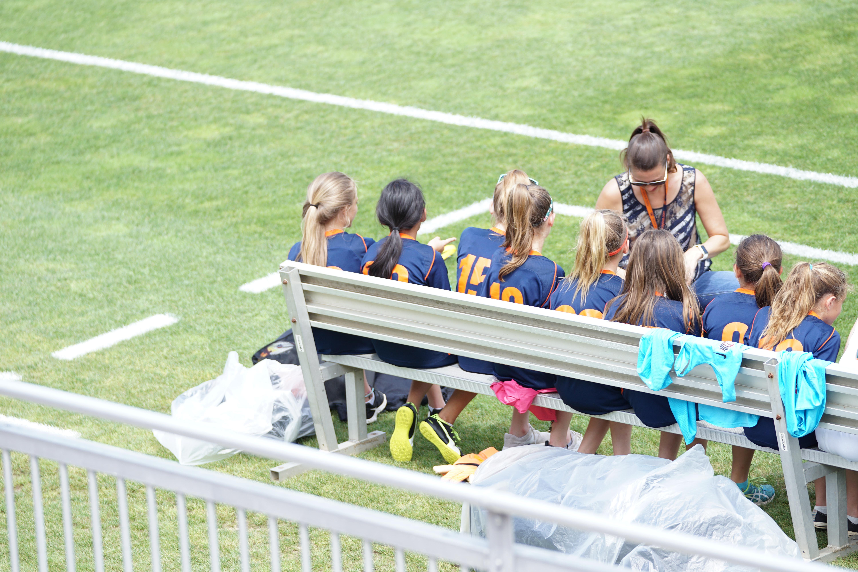 eight girls sitting on gray bench