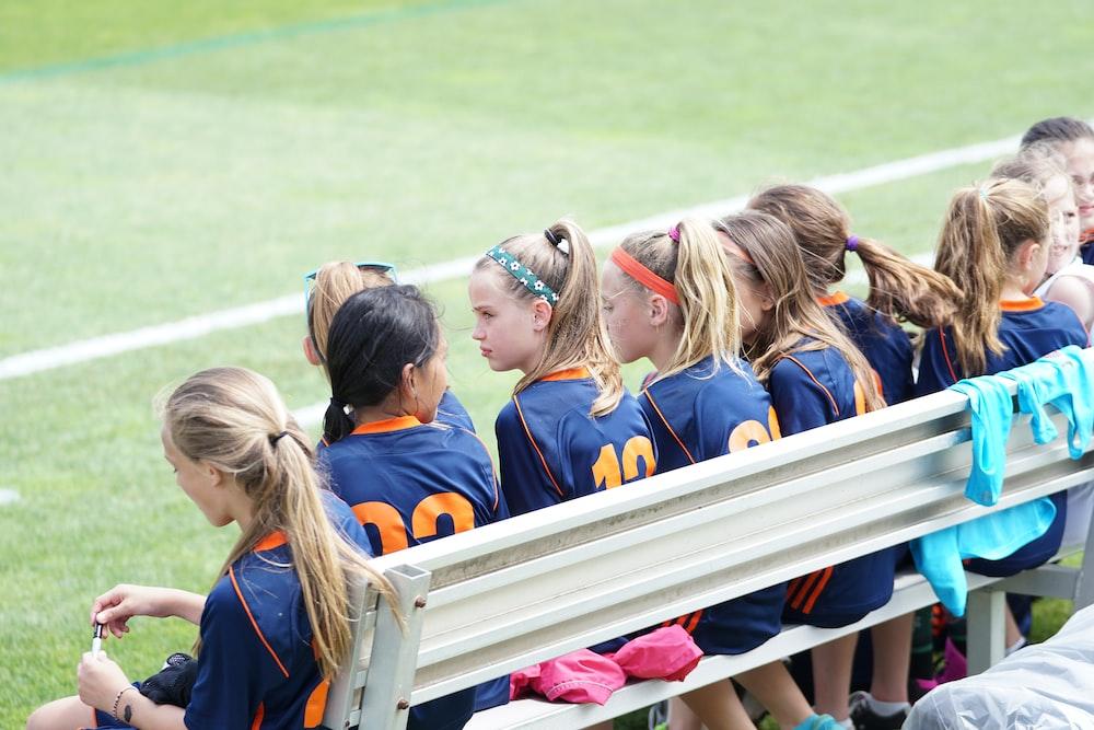 girls sitting on bench during daytime
