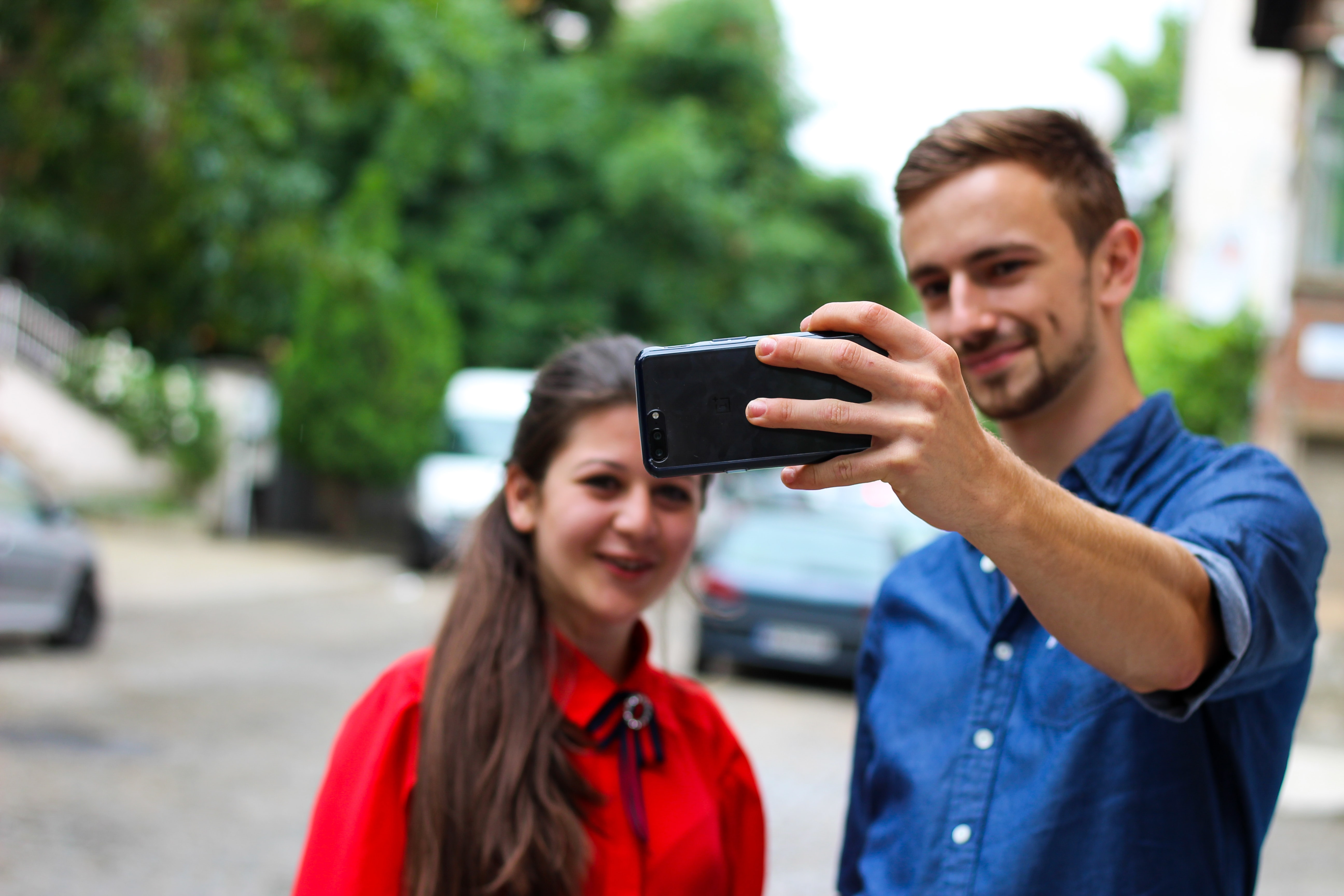 man standing beside woman holding smartphone