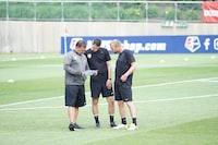 three men standing on football field