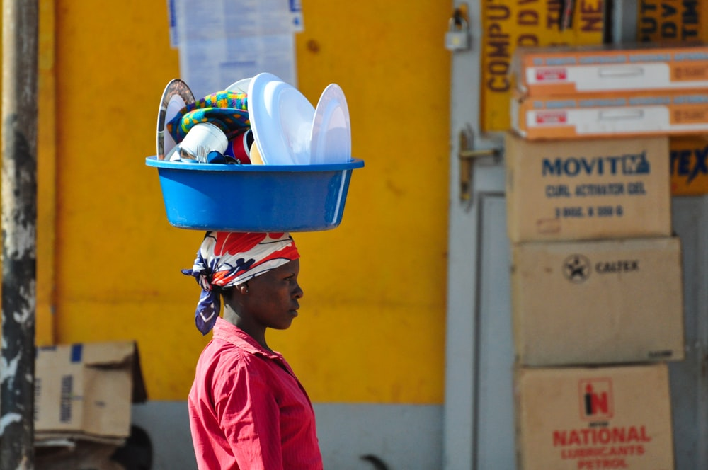 woman in red collared top carrying basin on head