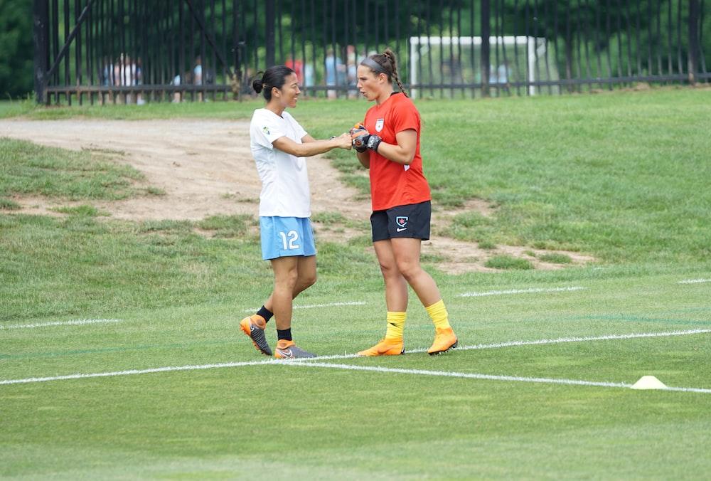 two women fist bumping on field