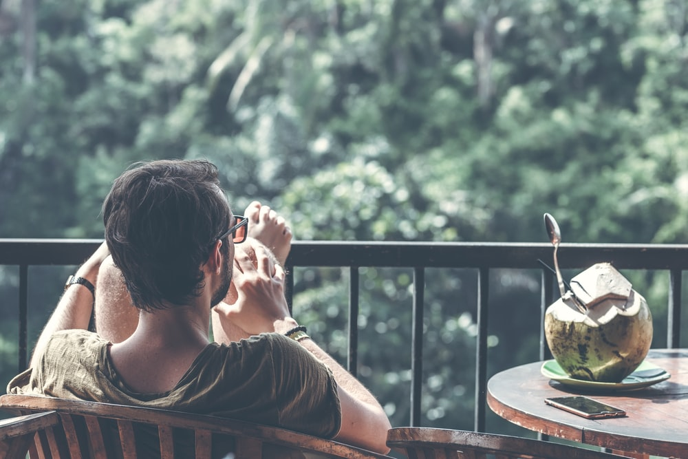 man sitting on armchair near table with opened coconut